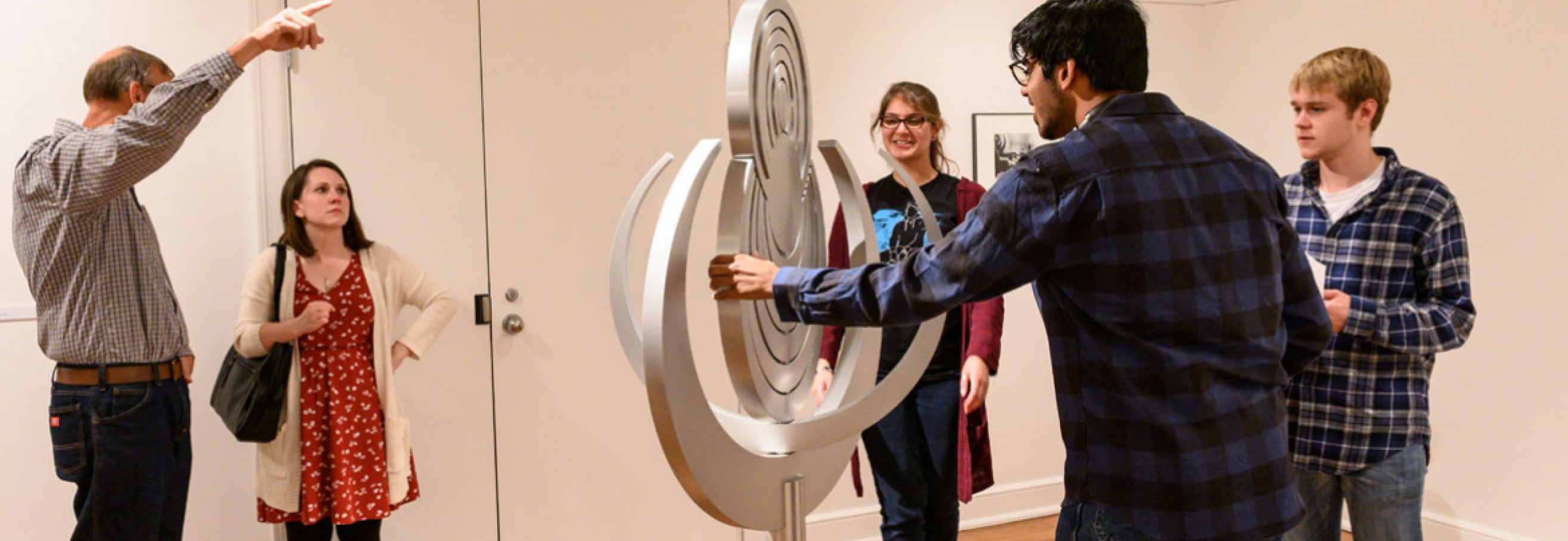 Students and faculty look at an artistic sculpture